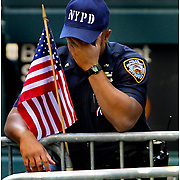 A NYPD officer breaks down momentarily as he mans a post near Ground Zero just days following the terrorist attack.