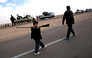 Libyan boy Amal Jamal holds a rifile as he walks with his father on the road where the rebels have staged their front line nearby the town of Ajdabiya which is still under the control of Qaddafi's government forces. (Photo by Heidi Levine/Sipa Press).