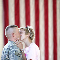 (red white and love)  --  Beneath the streaming red and white stripes of the American flag, a huge smile comes across the face of Alexandria Shivell as she shares one last kiss with her boyfriend Sgt. Carl Sorrels before he boards a buss for Wisconsin, en-route to Iraq with the Army National Guard's 81st Heavy Brigade Combat Team.        Monday, August 18, 2008        MZ Photo
