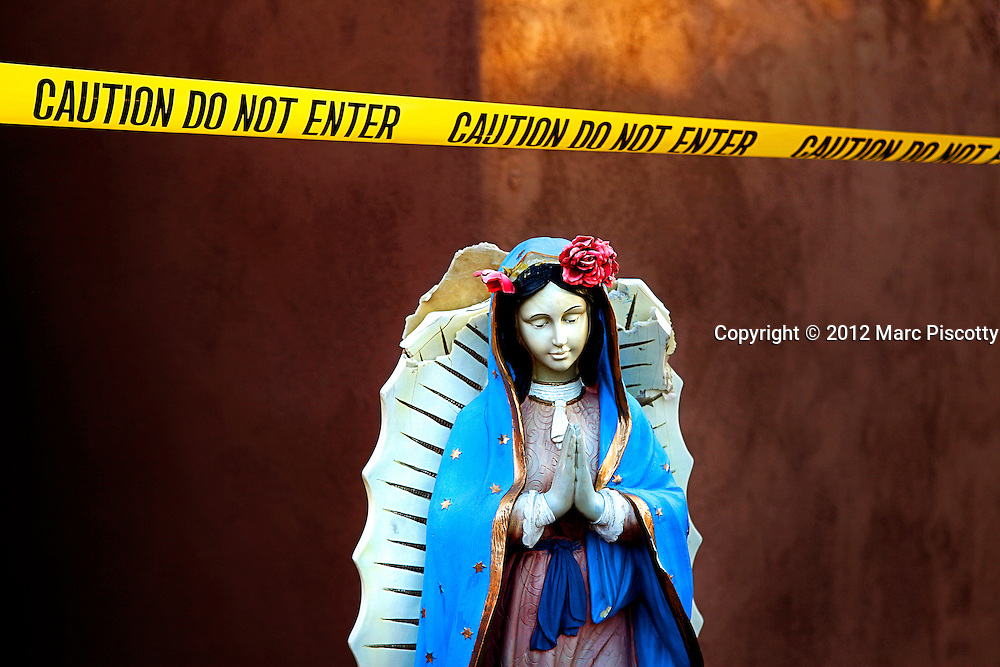 SHOT 12/30/11 5:32:11 PM - Crime scene tape and a statue of Our Lady of Guadalupe at the Capilla de Nuestra Senora de Guadalupe (Our Lady of Guadalupe Chapel) is located in historic Old Town Plaza in Albuquerque, New Mexico. It was established by Sister Giotto Moots in the early 1970's and was meant as an all-faiths chapel for artists seeking a spot for relaxation and reflection. It is now open to the public and is open 24 hours a day 365 days a year. (Photo by Marc Piscotty /  © 2012)