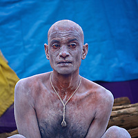 An Ash smeared Naga Sadhu who was recently converted to Naga Sadhu status. Naga Sadhus belong to the Shaiva sect, they have matted locks of hair and their bodies are covered in ashes like Lord Shiva.<br />