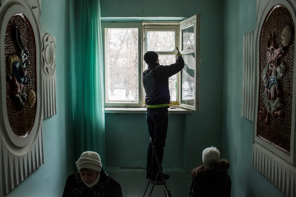 DONETSK, UKRAINE - JANUARY 23, 2015: A man weather seals a window inside School 337, which was struck and damaged two days earlier by a rocket attack in Donetsk, Ukraine. Schools in Donetsk have been closed this week due to increased fighting, and will remain closed indefinitely. After the rebels finally took control of the heavily contested airport in Donetsk from the Ukrainian Army, they have promised an offensive to extend their territory further. CREDIT: Brendan Hoffman for The New York Times