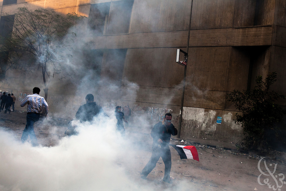Egyptian protestors try to escape a tear gas canister fired into their midst by nearby security forces during street battles November 21, 2011 near Tahrir square  in central Cairo, Egypt. Thousands of protestors demanding the military cede power to a civilian government authority clashed with Egyptian security forces for a third straight day in Cairo, with hundreds injured and at least 24 protestors killed.  (Photo by Scott Nelson)