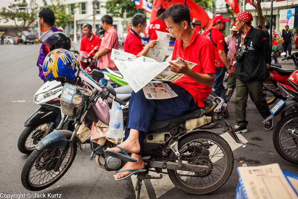"10 DECEMBER 2012 - BANGKOK, THAILAND:  Red Shirt protestors sit on their motorcycles and read the newspaper during a protest for constitutional reform on Ratchadamnoen Avenue in Bangkok Monday. The Thai government announced on Monday, which is Constitution Day in Thailand, that will speed up its campaign to write a new charter. December 10 marks passage of the first permanent constitution in 1932 and Thailand's transition from an absolute monarchy to a constitutional monarchy. Several thousand ""Red Shirts,"" supporters of ousted and exiled Prime Minister Thaksin Shinawatra, motorcaded through the city, stopping at government offices and the offices of the Pheu Thai ruling party to present demands for a new charter.      PHOTO BY JACK KURTZ"