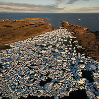 Canada, Nunavut Territory, Repulse Bay, Aerial view melting icebergs amid Harbour Islands on Hudson Bay at sunset on summer evening