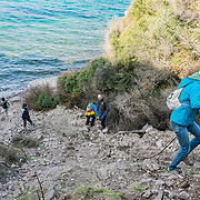 Some volounteers of the NGO Lighthouse Relief descend towards a small beach on the northern coast of Lesbo to clean it from all the life jackets and other stuff left by the refugees