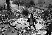 A girl is crossing a open sewage filled with garbage to get to another part of the French colony slum. .The pilling of garbage causes health hazards in the Christian community living in the slum.