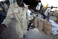 A man puts away his gun outside his shop in Abyei.