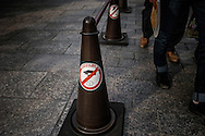 """A sign urges visitors to """"manner up"""" in English and with graphics showing a hand littering in the Gion entertainment and geisha quarter.  Kyoto, Japan."""