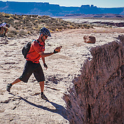 SHOT 10/15/16 3:23:08 PM - Tossing a rock over the edge along the White Rim Trail. The White Rim is a mountain biking trip in Canyonlands National Park just outside of Moab, Utah. The White Rim Road is a 71.2-mile-long unpaved four-wheel drive road that traverses the top of the White Rim Sandstone formation below the Island in the Sky mesa of Canyonlands National Park in southern Utah in the United States. The road was constructed in the 1950s by the Atomic Energy Commission to provide access for individual prospectors intent on mining uranium deposits for use in nuclear weapons production during the Cold War. Four-wheel drive vehicles and mountain bikes are the most common modes of transport though horseback riding and hiking are also permitted.<br /> (Photo by Marc Piscotty / &copy; 2016)
