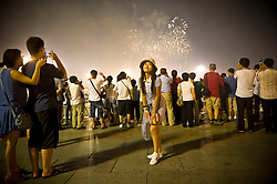 A Chinese girl posesin front of fireworks as they illuminate the sky next to the entrance of the Forbidden City during the closing ceremony of the Beijing 2008 Olympic Games  August 24, 2008. (Photo By Ami Vitale)