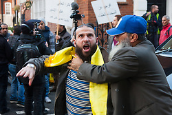 """Mayfair, London, November 28th 2014. A protest against Egypt's leader Al-Sisi descended into moinor scuffles as right wing """"patriots"""" from anti-Islamic group Britain First arrived to protest against the presence of Islamist preacher Anjem Choudary, who was recently arrestred as part of an ant-terror operation. Playing patriotic British Music, Britain First accused Muslims of worshiping a """"devil"""" and a """"paedophile prophet"""". Police had to intervene before hotheads on both sides became violent. PICTURED: A protest organiser, right, tries to prevent one of his comrades from approaching the embassy and risking arrest."""