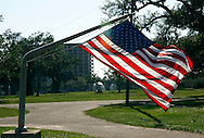 A flag pole bent over by hurricane Katrina holds the U.S. flag on the Mississippi Gulf of Mexico coast May 5, 2010.  Almost 5 years after hurricane Katrina laid the shore bare much remains to be rebuilt with another natural disaster - the BP oil spill - looming offshore.  REUTERS/Rick Wilking (UNITED STATES)