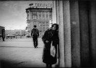 Exhausted woman positioned for handout beside St. Petersburg subway exit, Russia.