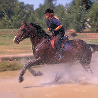 Girl running a horse through water