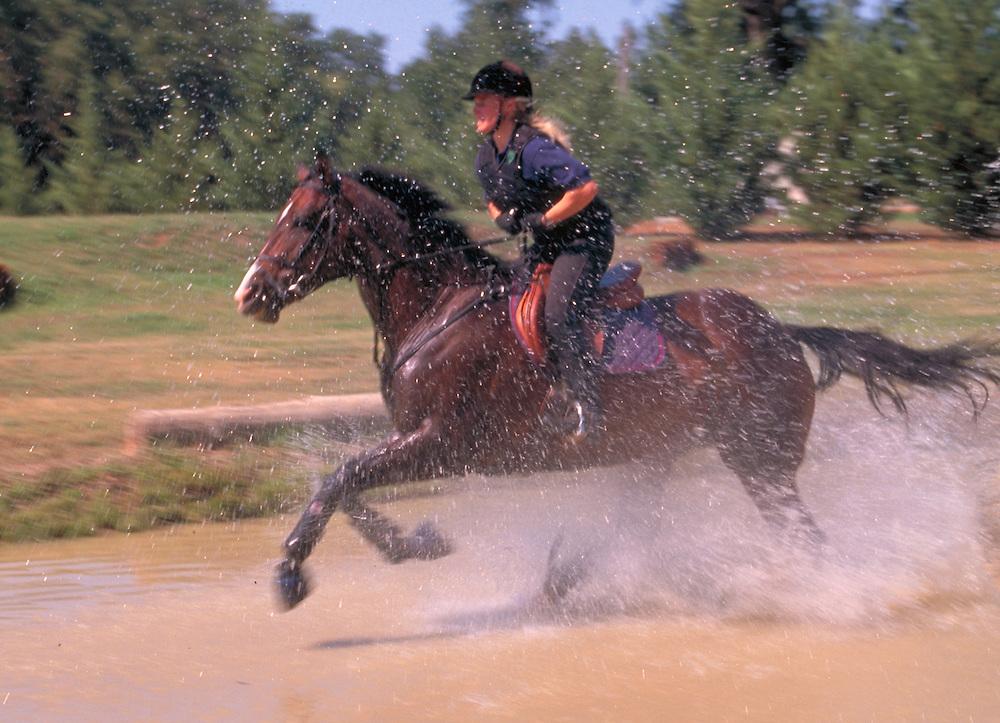 Girl running a horse through water