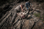 Jos&eacute; Pinguelo climbing the escarpment with the head of a deer.<br /> <br /> &quot;The Pose and the Prey&quot;<br /> <br /> Hunting in my imagination was always more like taxidermy &mdash; as if the prey was just a mere accessory of the hunter's pose for his heroic photograph &mdash; the real trophy.<br /> <br /> When I decided to document the daily lives of Portuguese hunters, I had in my memory the &quot;clich&eacute;&quot; from the photographer Jos&eacute; Augusto da Cunha Moraes, captured during a hippopotamus hunt in the River Zaire, Angola, and published in 1882 in the album Africa Occidental. The white hunter posed at the center of the photograph, with his rifle, surrounded by the local tribe.<br /> <br /> It was with this clich&eacute; in mind that I went to Alentejo, south of Portugal, in search of the contemporary hunters. For several months I saw deer, wild boar, foxes. I photographed popular hunting and private hunting estates, wealthy and middle class hunters, meat hunters and trophy hunters. I photographed those who live from hunting and those who see it as a hobby for a few weekends during the year. I followed the different times and moments of a hunt, in between the prey and the pose, wine and blood, the crack of gunfire and the murmur of the fields .<br /> <br /> I was lucky, I heard lots of hunting stories. I found an essentially old male population, where young people are a minority. Hunters, a threatened species by aging and loss of economic power caused by the crisis in the South of Europe.<br /> <br /> The result of this project is this series of contemporary images, distant from the &quot;cliche&quot; of 1882.<br /> <br /> &mdash; Antonio Pedrosa