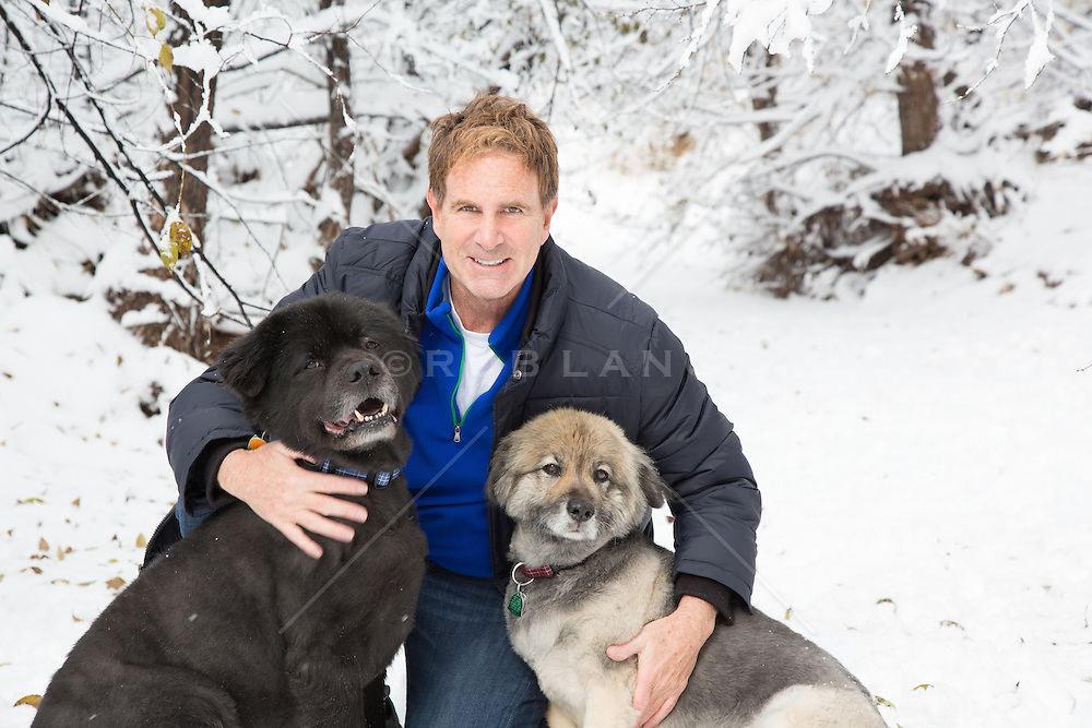man and his two dogs outdoors in the snow