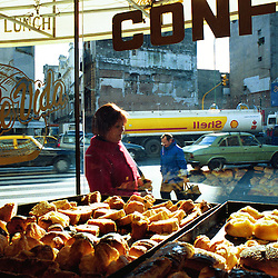 BUENOS AIRES, ARGENTINA:  A woman passes by a local pastry shop in Buenos Aires, Argentina..(Photo by Ami Vitale)
