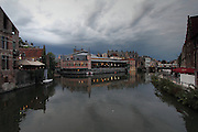 Dark clouds in the distance behind the old town of Ghent, at dusk. In the middle is the old Fish Market that has been converted into an expensive restaurant