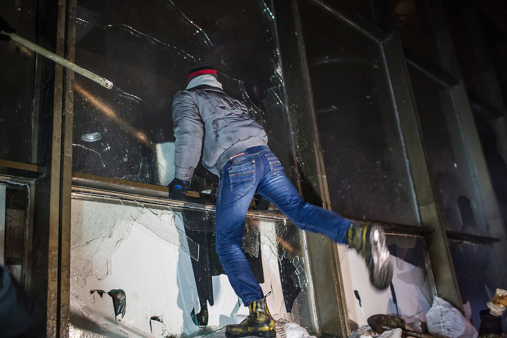 KIEV, UKRAINE - JANUARY 25: An anti-government protester kicks in a window of the Ukrainian House, which protesters attempted to take over, on January 25, 2014 in Kiev, Ukraine. After two months of primarily peaceful anti-government protests in the city center, new laws meant to end the protest movement have sparked violent clashes in recent days. (Photo by Brendan Hoffman/Getty Images) *** Local Caption ***