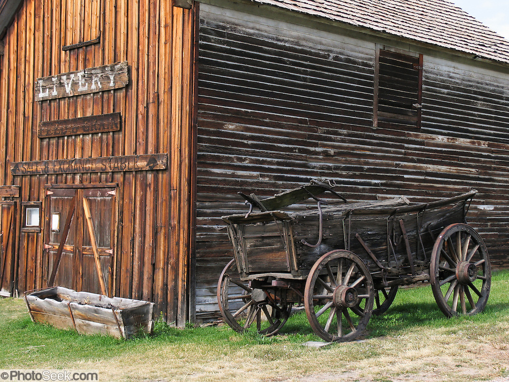 "A wagon with iron-bound wooden carriage wheels stands outside a late 1800s livery stable preserved at the outdoor history museum of Nevada City, Montana, USA. Nevada City was a booming placer gold mining camp from 1863-1876, but quickly declined into a virtual ghost town. This fascinating town inspires you to imagination what life must have been like in early Montana when gold was discovered at nearby Alder Gulch. More than 90 buildings from across Montana have been gathered for preservation at Nevada City, mostly owned by the people of the State of Montana, and managed by the Montana Heritage Commission. In 2001, the excellent PBS television series ""Frontier House"" used one of the buildings and its furnishings to train families in re-creating pioneer life. A miner's court trial and hanging of George Ives in the main street of Nevada City was the catalyst for forming the Vigilantes, a group of citizens famous for taking justice into their own hands in 1863-1864. Directions: go 27 miles southeast of Twin Bridges, Montana on Highway 287."