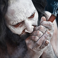 An Ash smeared Naga Sadhu smoking pot during the Kumbh Mela, 2010.<br />