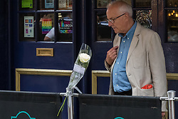 """Compton Street, Soho, London, June 13th 2016. A pair of white roses, a solemn memorial to the 50 people killed at gay club Pulse in Orlando on 12 June, is attached to the balustrade outside The Admiral Duncan, a LGBT-friendly bar that knows too well the price of homophobia, bombed by Neo-Nazi David Copeland on 30 April 1999, killing three people and wounding 70. The message on the card reads, """"Compton Street, Soho, London, June 13th 2016. A pair of white roses, a solemn memorial to the 50 people killed at gay club Pulse in Orlando on 12 June, is attached to the balustrade outside The Admiral Duncan, a LGBT-friendly bar that knows too well the price of homophobia, bombed by Neo-Nazi David Copeland on 30 April 1999, killing three people and wounding 70. The message on the card reads, """"To Orlando, LOVE IS LOVE! Soho stands with you."""" and is signed """"James and Talia"""". PICTURED: A man crosses himself as he looks at the roses."""