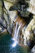 """A pretty waterfall plunges under the natural bridge in Big Collapse Doline (Velika dolina) in Skocjan Caves (Skocjanske jame) Regional Park, Slovenia, Europe. Skocjan Caves feature a river raging through one of the world's largest caverns, waterfalls, speleothems (cave formations such as dripstone: stalactites and stalagmites), and twisty paths through eleven chambers over six kilometers. From a large-scale karst drainage, the Reka River has carved and dissolved dramatic subterranean passages through limestone over several million years. Archaeological finds in Tominceva Cave (Ozka spilja, near the natural entrance of Skocjan Caves) indicate human occupation here from 3000 BC to 1700 BC. Modern tourism began in Skocjan Caves by 1819. Karst topography is a geologic formation of dissolving bedrock. Our word for """"karst"""" likely evolved from the Slovene noun kras and earlier proper noun Grast, referring to Slovenia's Karst Plateau. Skocjan Caves are near Divaca, in the Littoral region of the Republic of Slovenia. UNESCO has listed Skocjan Caves as a World Heritage Site."""
