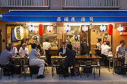 Small outdoor restaurant on street in the evening in Rokku entertainment district of Asakusa adjacent to SensoJi shrine in Tokyo Japan