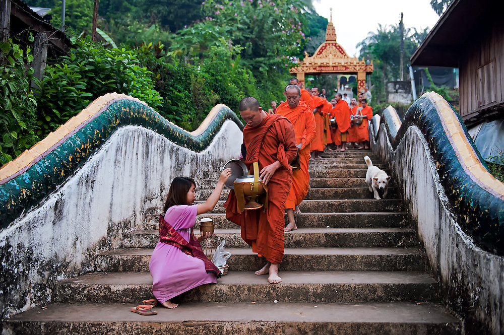 Novices and monks collecting alms in Hua Xia, Laos.