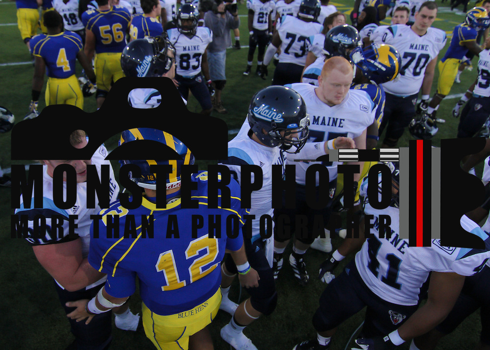 Delaware quarter back Trent Hurley #12 sakes hands with University of Maine Defensive Linemen Matthew Pellerin (90) after a Week 6 26 - 3 loss against Maine.