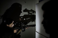 """SYRIA, ALEPPO. A Kurdish female fighter from the """"Popular Protection Units"""" (YPG) aims at Syrian government forces inside a building in the majority-Kurdish Sheikh Maqsud district of the northern Syrian city of Aleppo. ALESSIO ROMENZI"""