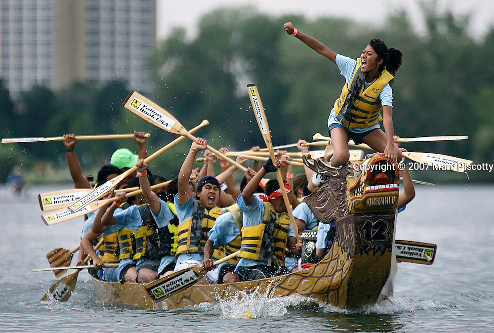 SHOT 7/29/2007 - Flag catcher Valerie Amphonephong (on bow of boat), 13, of Aurora raises her arm in victory as the rest of her Lao Buddhist Temple teammates celebrate their win in the championship of the youth division of the 2007 Colorado Dragon Boat Festival. The team won two races in a row because their opponent in the championship hadn't lost a race in the double elimination format of the races. The sport of Dragon boat racing is over 2000 years old and features teams of 18 paddlers - nine men and nine women plus someone to steer the boat - all rowing in sync to the beat of a drum and racing to a flag 200 meters away on Sloan's Lake in Denver, Co. Founded in 2001 to celebrate Denver?s rich Asian Pacific American culture, the Colorado Dragon Boat Festival has become the region?s fastest growing and most acclaimed new festival. Festival-goers get to explore the Asian culture through demonstrations, crafts, shopping, eating, and the growing sport of dragon boat racing. .(Photo by Marc Piscotty / © 2007)