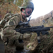 Platoon Sergeant 'Panky' yells at his men to take cover as enemy grenades explode nearby. British soldiers from 1PWRR (Princess of Wales's Royal Regiment) are involved in an ongoing series of Operations called Tora Pishaw aimed at disrupting insurgent activity in their AO (Area of Operations). During the most recent 4 day operation the soldiers regularly came under fire from insurgents using small arms, belt fed machine guns and UGL's (Under Slung Grenade Launchers). The soldiers returned fire using shallow trenches on the edges of ploughed fields or irrigation ditches as cover. Nad I Ali North, Helmand Province, Afghanistan on the 13th of November 2011.