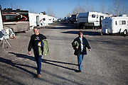 """Workampers"" Dan, left, and Vicky Suiker walk back to their RV from after showering at the Desert Rose RV Park on their day off from their seasonal job at the Amazon warehouse in Fernley, Nevada, December 13, 2011. CREDIT: Max Whittaker/Prime for The Wall Street Journal.AMAZONTOWN"