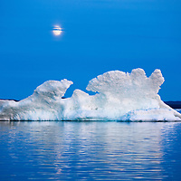 Canada, Nunavut Territory, Moon rises behind melting iceberg in Frozen Channel at northern edge of Hudson Bay near Arctic Circle