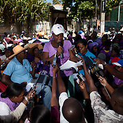 A woman from Haitian Women's Solidarity (SOFA) reads a declaration in front of the Ministry for the Status and Condition of Women. (Photo by Ben Depp)
