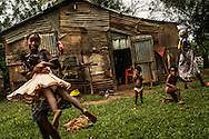 MONTE PLATA PROVINCE, DOMINICAN REPUBLIC - OCTOBER 11, 2013: Children born in the Dominican Republic to Haitian parents, and who are affected by judgment TC/0168 that will revoke their citizenship, play outside of their home in an impoverished batey in Monte Plata province.