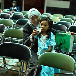 A young girl sits with her mother after her circumcision in Bandung, Indonesia on April 23, 2006. The families of 248 girls were given money to have their children circumcised in a mass circumcision celebration timed to honour the Prophet Mohammed's birthday. While religion was the main reason for circumcisions, it is believed by some locals that a girl who is not circumcised would have unclean genitals after she urinates which could lead to cervical cancer. It is also believed if one prays with unclean genitals their prayer won't be heard. The practitioners used scissors to cut the hood and tip of the clitoris. The World Health Organization has deemed the ritual unnecessary and condemns such practices.