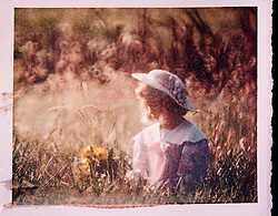polaroid transfer young female girl with bonnet flowers field