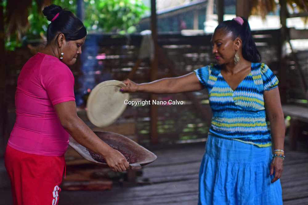 Virgilia and Kathiana preparing natural cacao drink at Bribri tribe house. <br />