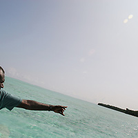 Catholic Priest Father Boniface Besco points the way, guiding a boat through the reef, towards Han Island, Carteret Atoll, Papua New Guinea, on Sunday, Dec. 10, 2006. Rising sea levels have eroded much of the coastlines of the low lying Carteret islands (situated 80km from Bougainville island, in the South Pacific), and waves have crashed over the islands flooding and destroying what little crop gardens the islanders have. Food is in short supply, banana and swamp taro crops are failing due to the salt contamination of the land, and the islanders live on a meagre one meal per day diet of fish and coconut. There is talk by the Autonomous Region of Bougainville government to relocate the Carteret Islanders to Bougainville island, but this plan is stalled due to a lack of finances, resources, land and coordination.