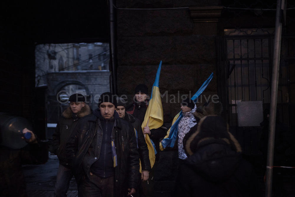Anti-government protesters stand guard at one of the barricades defending Maidan Square against police and government supporters on December 12, 2013 in Kiev, Ukraine. Thousands of people have been protesting against the government since a decision by Ukrainian president Viktor Yanukovych to suspend a trade and partnership agreement with the European Union in favor of incentives from Russia was made recently.