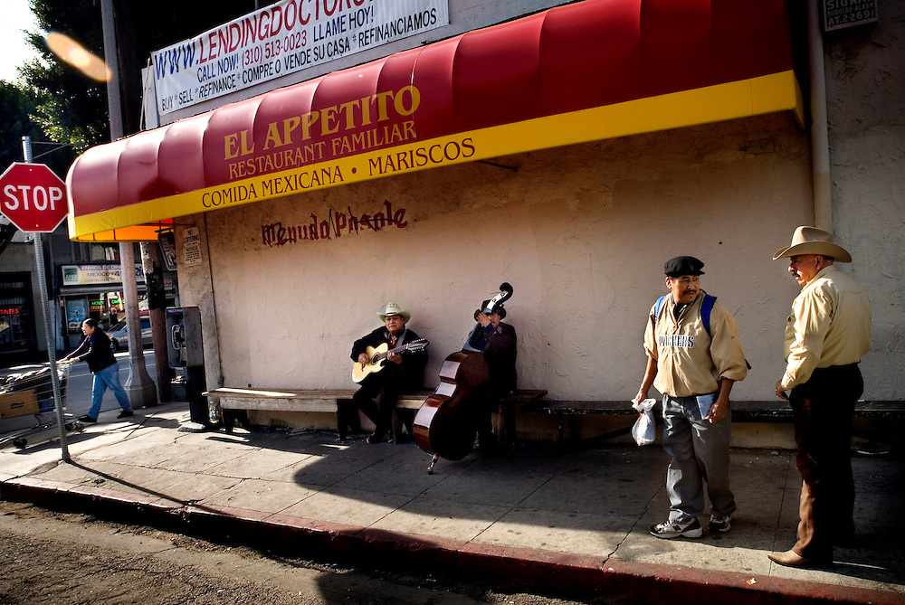 Mexican musicians (Mariano Cruz, playing bass) playing at a street corner in a mexican neighborhood in East Los Angeles...Photographer Chris Maluszynski /MOMENT