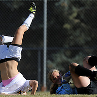 Bend's Janet Johnson (23) falls after colliding with the West Albany goal keeper during the first half Tuesday in Bend.