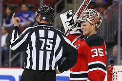Oct 21, 2014; Newark, NJ, USA; Linesman Derek Amell (75) and New Jersey Devils goalie Cory Schneider (35) talk during a break in the action during the first period at Prudential Center.