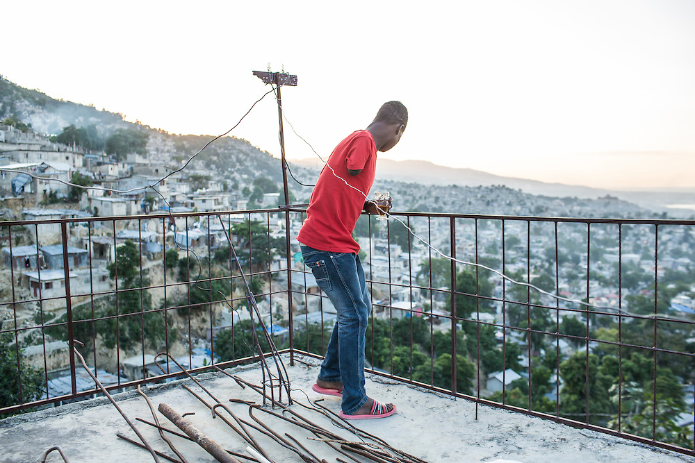 John Legagneuk looks over the Tapis Rouge neighborhood at sunset on Friday, December 19, 2014 in Port-au-Prince, Haiti. Legagneuk lost his arm in a car accident in 2012.