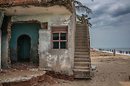 House abandoned because of the advancing sea.  The Bay of Bengal has undercut this house, long after it was struck by the 2004 Asian Tsunami.  Up and down this coast of Southern India, the sea is eroding beaches and cutting into inhabited land.  Pondicherry, India.