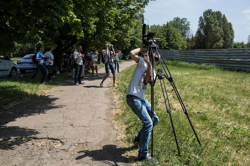 DONETSK, UKRAINE - MAY 26: A journalist films as a helicopter flies low over the Donetsk airport, scene of an hours-long battle between pro-Russian separatists and Ukrainian forces, on May 26, 2014 in Donetsk Ukraine. A day after businessman Petro Poroshenko won Ukraine's presidential election, separatists occupied the airport, leading to a military response. (Photo by Brendan Hoffman/Getty Images)